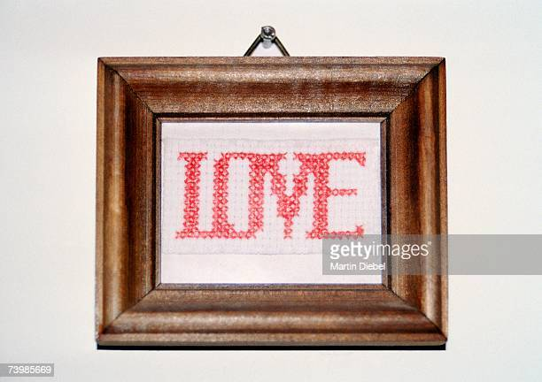 Love cross-stitching in a frame and hanging on a wall