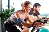 Close-up portrait of gym members participating in a exercising class while training together at fitness centre. Sporty woman listening music at her mobile phone.