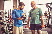 Senior man and fitness instructor talking in gym.