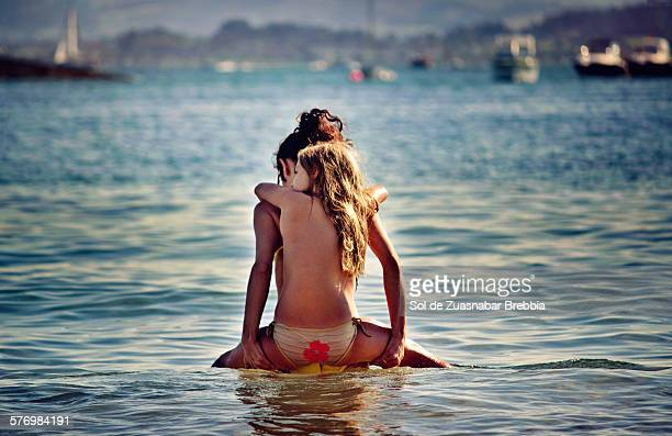 Love. Girl on her mother's back in the sea