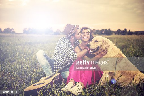 Love hipster couple in field exchange tenderness : Stock Photo