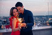 Couple celebrate New year on top of building.