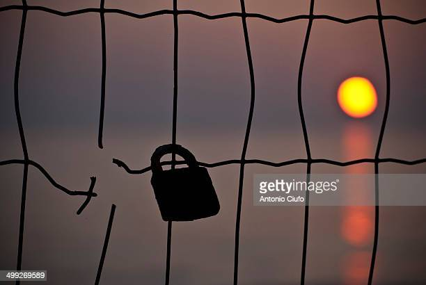 Love lock on a fence with sunset