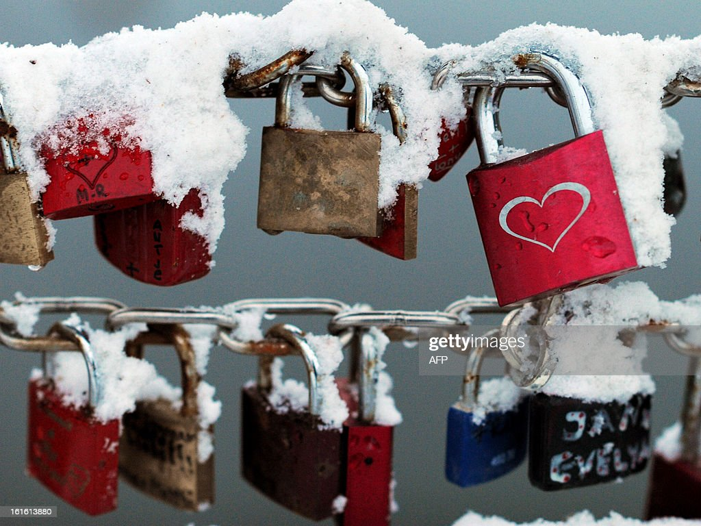 Love locks covered with snow are pictured on a bridge on February 12, 2013 in Luebeck, northern Germany.