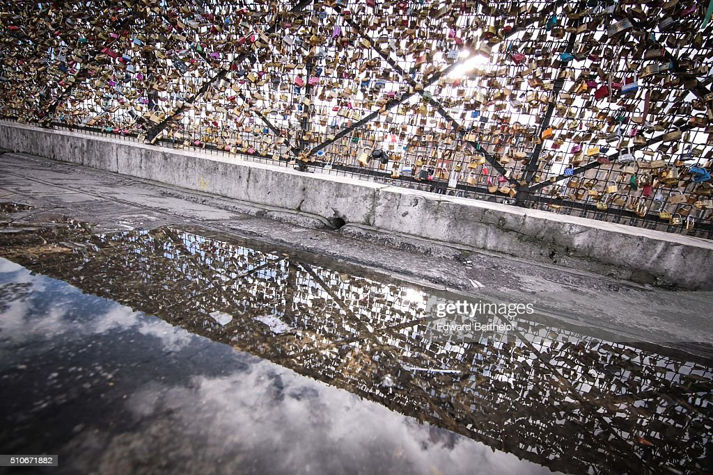 Love locks reflecting into a water puddle on Pont Neuf on February 7 2016 in Paris France