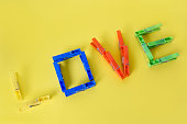 love message written wtih colored clothes pegs on yellow background