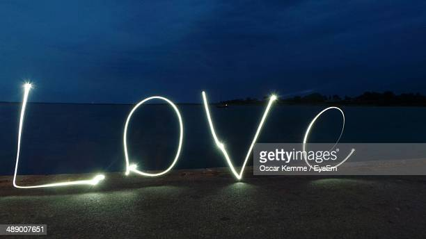 Love neon sign against sea at night