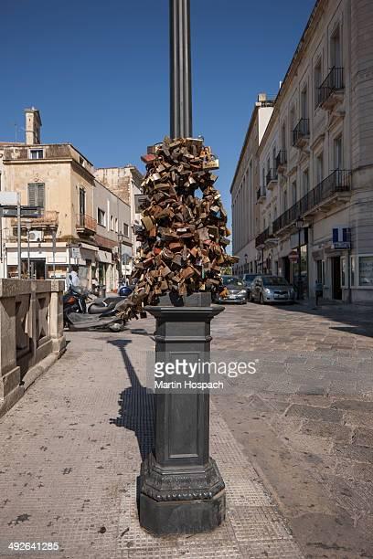 Love padlocks hanging on pole near street