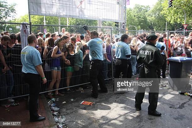 People mourn their friend who died in a stampede at the Love Parade techno festival police and security push back the people