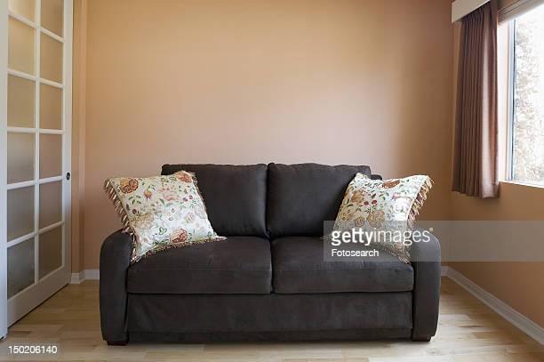 Love seat in peach colored room