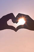 Romantic silhouette hand in heart shape with sunshine