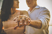 Cute couple holding hands show off a beautiful diamond engagement ring, romance, love and jewelry