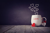 Love written on a mug with hearts concept for Valentines day or Mothers day background with copy space