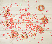 Te Quiero meaning I Love You in Spanish written with the block letters covered with red heart shaped confetti over the wooden background