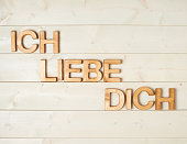 Ich Liebe Dich meaning I Love You in German written with the block letters over the wooden background