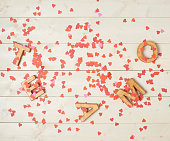 Te Amo meaning I Love You in Spanish written with the block letters covered with red heart shaped confetti over the wooden background