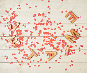 Je T'aime meaning I Love You in French written with the block letters covered with red heart shaped confetti over the wooden background