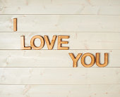 I love you composition of the block letters over the wooden background