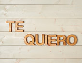 Te Quiero meaning I Love You in Spanish written with the block letters over the wooden background