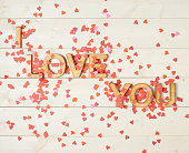 I love you composition of the block letters covered with red heart shaped confetti over the wooden background