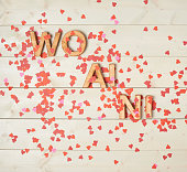 Wo Ai Ni meaning I Love You in Chinese written with the block letters covered with red heart shaped confetti over the wooden background