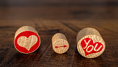 Love You symbols on 3 oval pieces of cork, with red hart, pointing arrow on You in red hart, Valentine's Day card, love letter, graphic idea on vintage oak panels fading in distance, front view