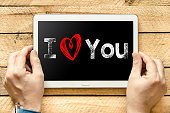 Hands with Tablet PC with text I love you on wooden background