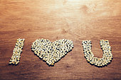 """I love you"" symbol made out of little wooden hearts on a wooden background. Love concept."