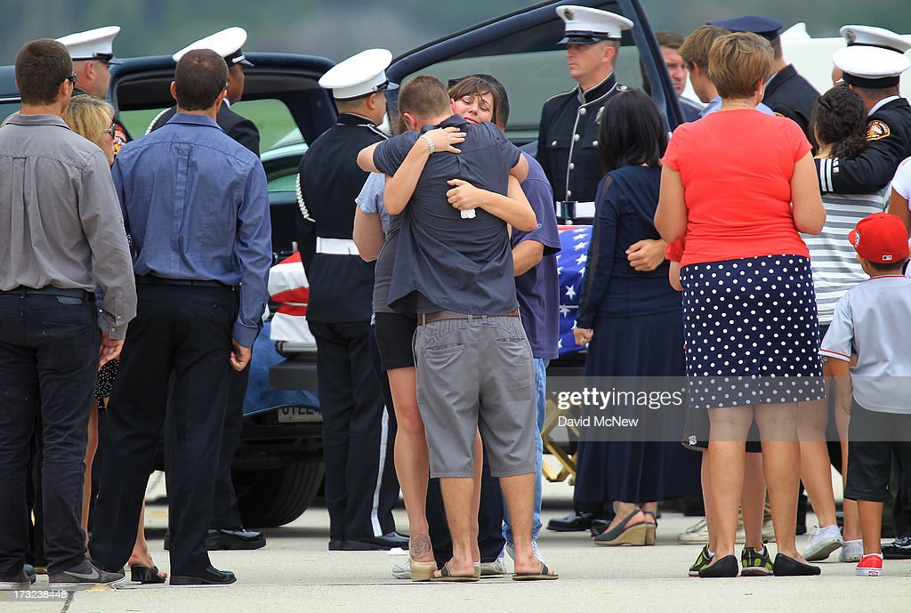 Loved ones grieve at the casket carrying the body of Kevin Woyjeck after arriving aboard a C-130 transport plane as two of the nineteen firefighters killed fighting the Yarnell Fire in Arizona arrive to the Joint Forces Training Base, Los Alamitos Air Field on July 10, 2013 in Los Alamitos, California. The memorial ramp ceremony, coordinated in part by the California Fire Foundations Last Alarm Service Team, honors Granite Mountain Interagency Hotshot Crew members 21-year-old Kevin Woyjeck and 20-year-old Christopher MacKenzie.