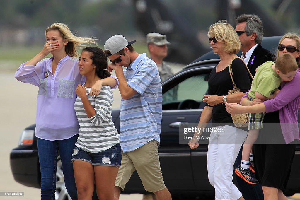 Loved ones walk from the casket carrying the body of Kevin Woyjeck after arriving aboard a C-130 transport plane as two of the nineteen firefighters killed fighting the Yarnell Fire in Arizona arrive to the Joint Forces Training Base, Los Alamitos Air Field on July 10, 2013 in Los Alamitos, California. The memorial ramp ceremony, coordinated in part by the California Fire Foundations Last Alarm Service Team, honors Granite Mountain Interagency Hotshot Crew members 21-year-old Kevin Woyjeck and 20-year-old Christopher MacKenzie.