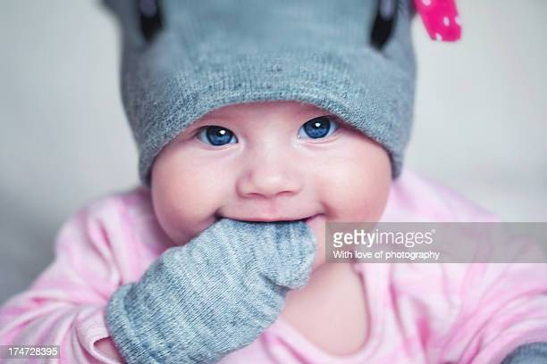 Lovely baby girl in a funny hat and mittens