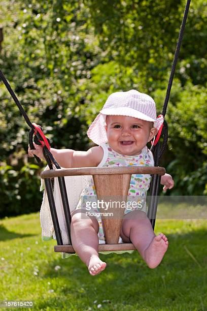 Lovely baby girl sitting in a swing