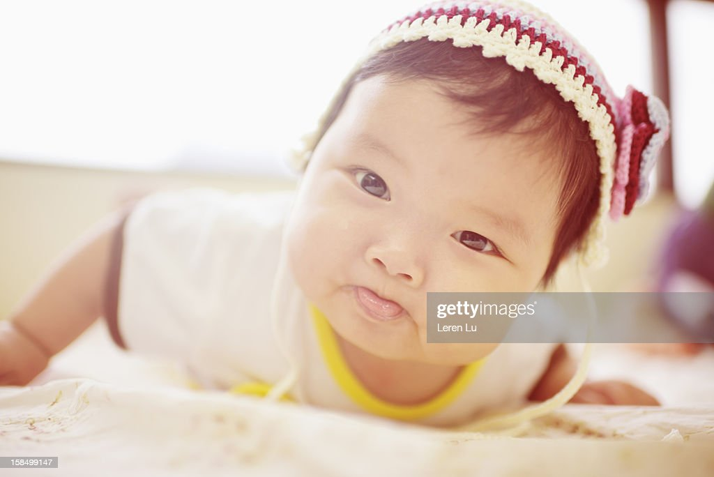 Lovely baby is crawling on the bed : Stock Photo