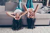 Lovely cheerful happy mother and playful little daughter with long hair are lying upside down on a couch and making binoculars with their fingers