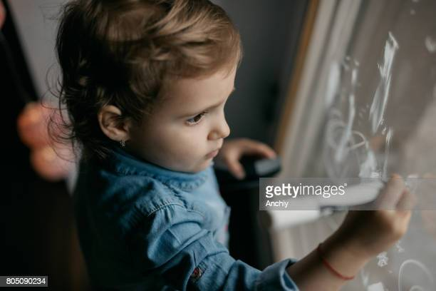 A lovely child is drawing on the window