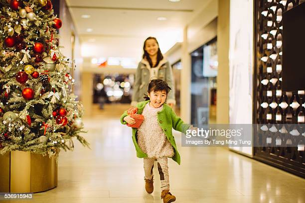 Lovely child playing joyfully with mom at mall