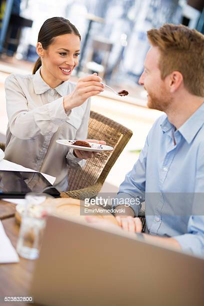 Lovely couple eating dessert in cafe