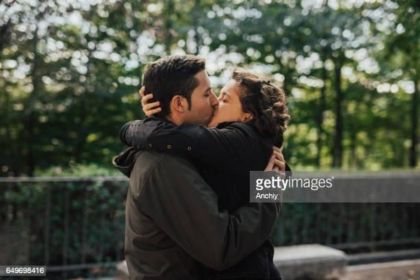 Encantadora pareja besándose en el parque público
