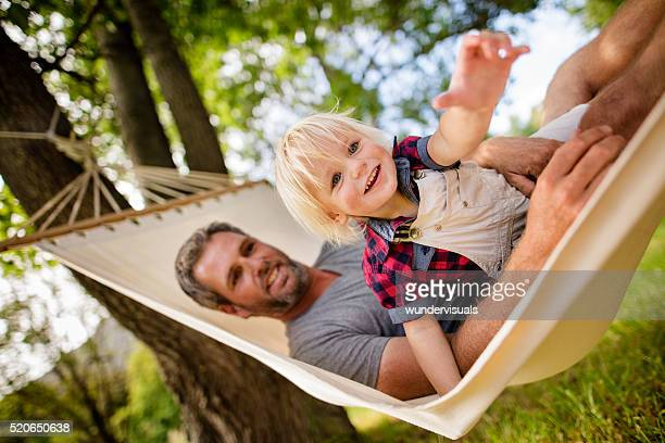 Lovely dad plays with his blond child on a hammock