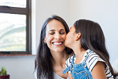 Young daughter kissing mother on cheek. Multiethnic little girl giving kiss to happy mother. Lovely daughter kissing cheerful mother on cheek at home.