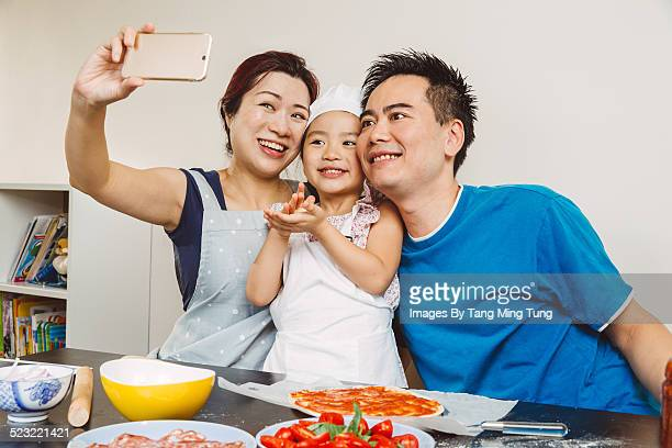 Lovely family taking selfies while cooking