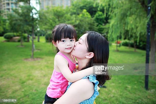 Lovely girl as her mother kisses her on the cheek