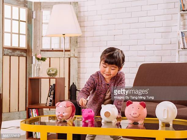 Lovely girl inserting coins into piggy banks