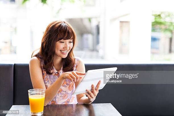 Lovely girl using ipad in a cafe