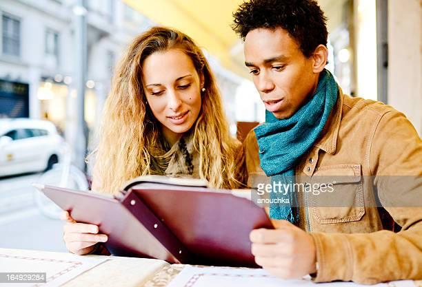 Schöne interracial paar lesen Menü im Café im Freien