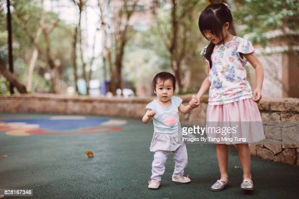 Lovely little daughter holding hands with her little sister and teaching her to walk in a playground joyfully.