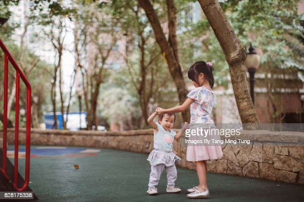 Lovely little daughter holding hands with her little sister playing with her while teaching her to walk in a playground joyfully.