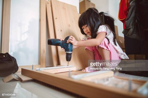 Lovely little girl assembling furnitures by herself using an electric screwdriver