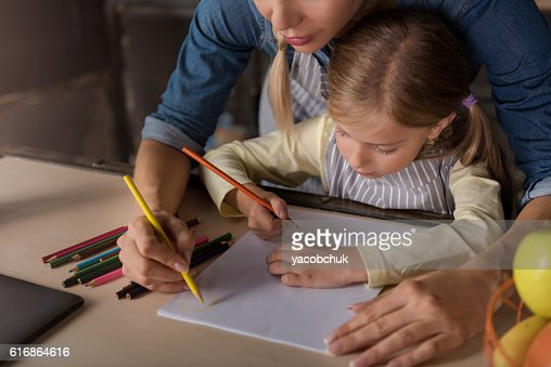 Lovely little girl drawing with her mother in the kitchen : Stock Photo