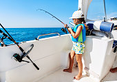 Lovely little girl with a fishing rod fishing on the boat